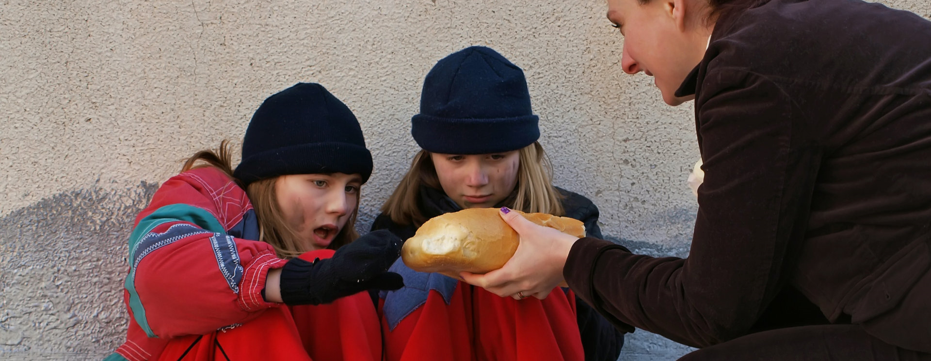 woman giving bread to the kids